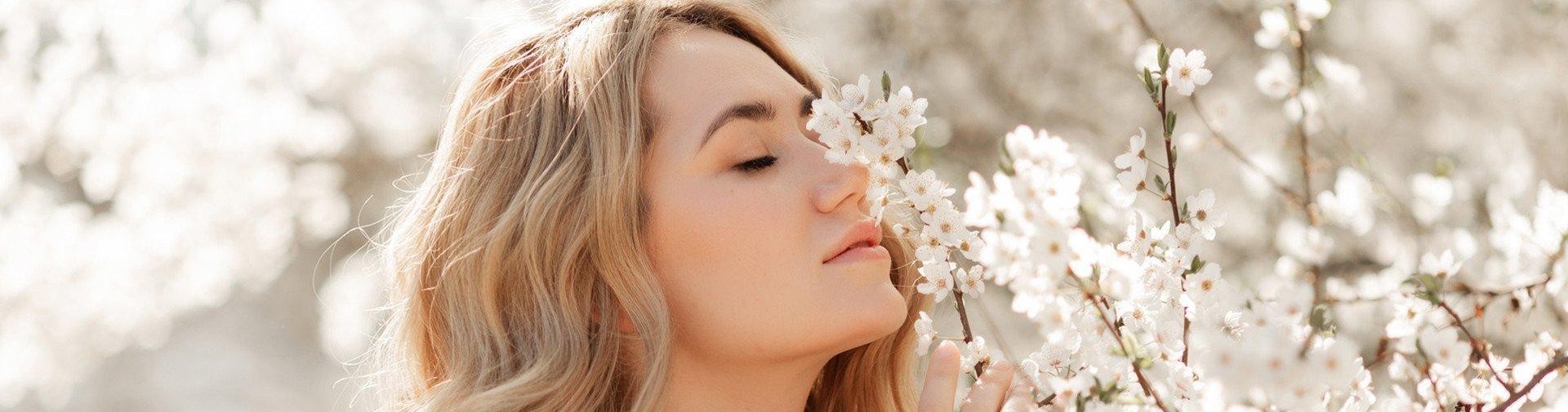 [Translate to Deutsch (Schweiz):] Frau riecht an frischen Blüten eines Baums